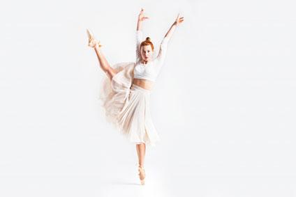 右足を高く上げて踊っている女性
