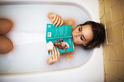 お風呂の中で本を読んでいる女性
