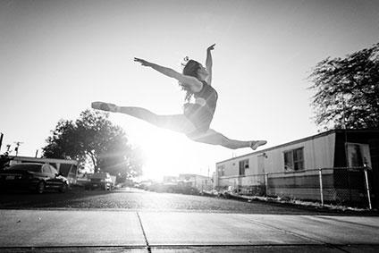 トウシューズを履き、道端でジャンプしている女性