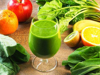 コップに入ったグリーンジュースとそれを取り囲むたくさんの野菜と果物