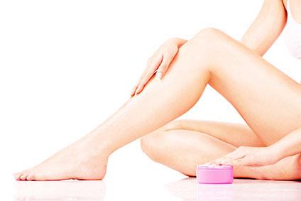 脚に保湿クリームを塗っている女性