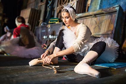 トウシューズを履こうとしているオデット役のバレリーナ