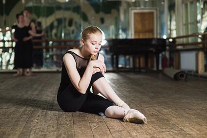 スタジオの床に座っているバレリーナ