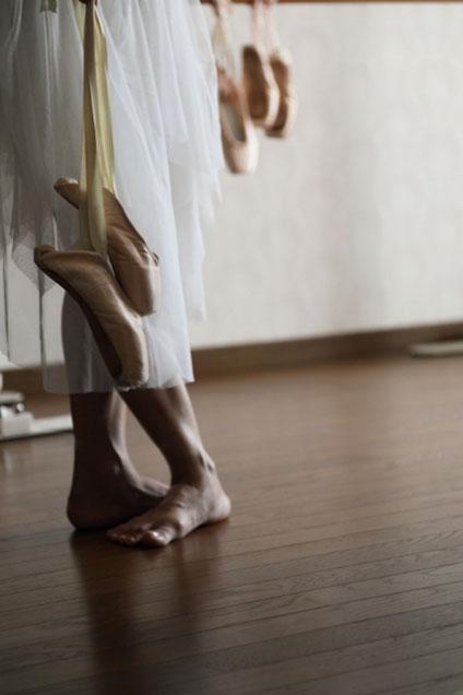 トウシューズを持っている裸足のバレリーナ