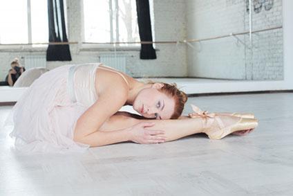 床に座っているバレリーナ