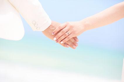 結婚式の新郎新婦が手を握り合っているところ