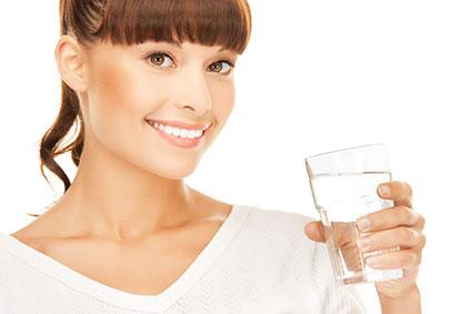 水の入ったコップを持っている女性