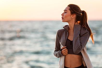 スポーツウェアを着て、海辺に佇む女性