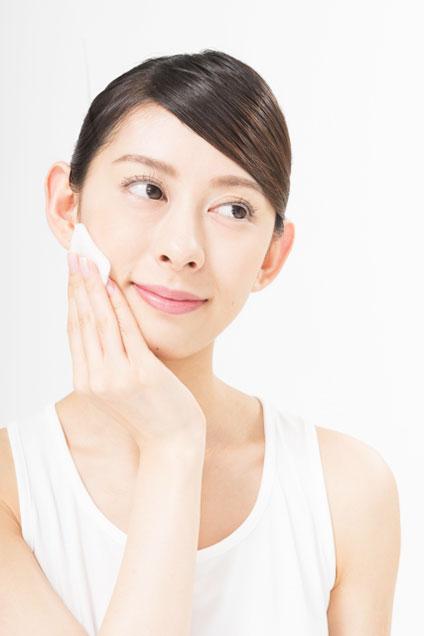 コットンで化粧水を馴染ませている女性