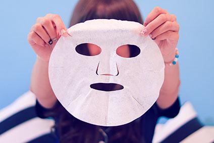 フェイスマスクを持つ女性